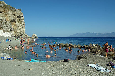 People bathing in the thermal springs in the sea at Agios Fokas, Kos, Greece