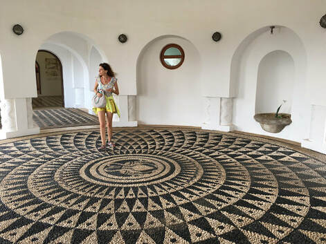 Woman standing on black and white mosaic pebble floor in Kalithea Spa, Rhodes, Greece - copyright Sarah Tastsidis
