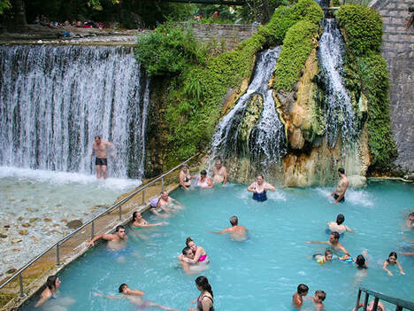 People swimming in Loutra Pozar natural spa and a man standing under a waterfall, Aridea, Greece