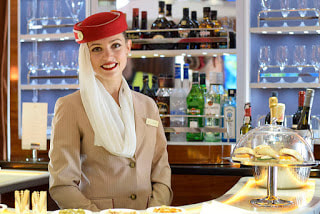Emirates Airline hostess at the bar - By Brussels Airport [CC BY-SA 2.0  (http://creativecommons.org/licenses/by-sa/2.0)], via Wikimedia Commons