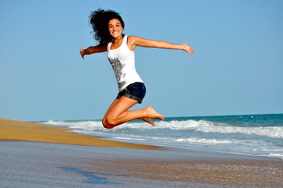 Woman jumping up on a beach - fitness