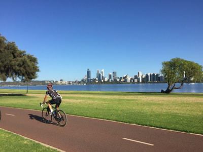Cyclist in Victoria Park with Perth city in the background, Western Australia