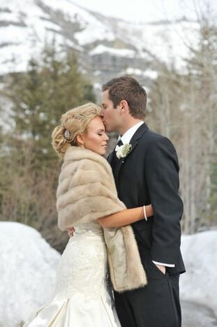 Bride and groom hugging against backdrop of snowy mountains