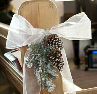 Pine cones, branch and white voile pew end decoration