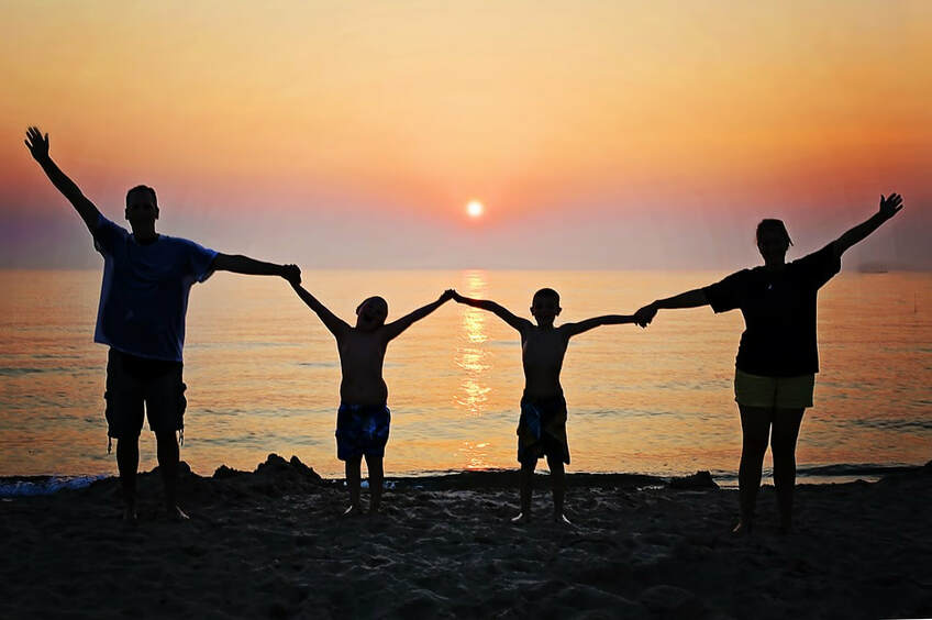 Happy family of four holding hands raised in the air on a beach at sunset