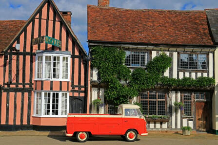 Medieval buildings in Lavenham with a red VW camper van in front