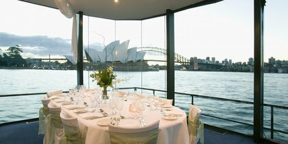Wedding table on boat with window looking out on Sydney opera house and harbour bridge