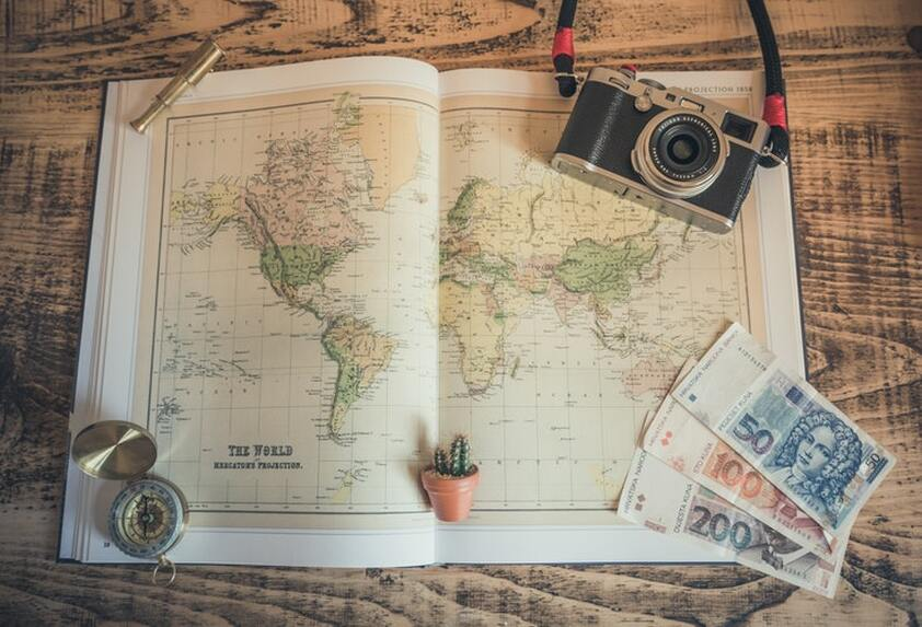 Travel planning - table with atlas, money, compass and camera