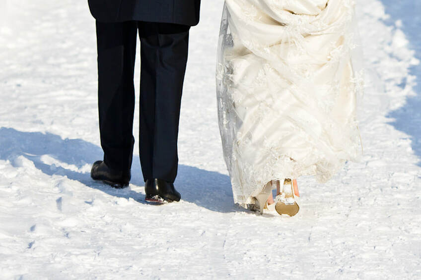 Bride and groom walking in snow - legs only