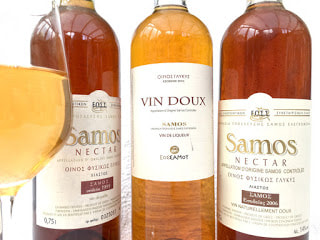 Three bottles of Muscat of Samos with a glass full of the wine